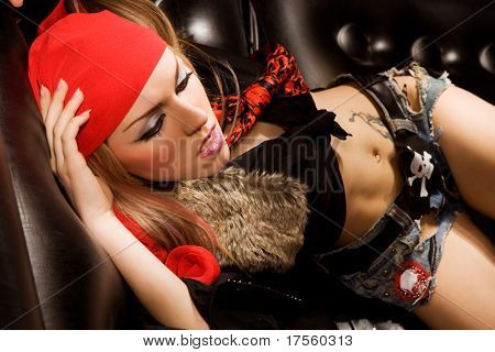 Sexy model wearing pirate outfit and red boots on black leather sofa