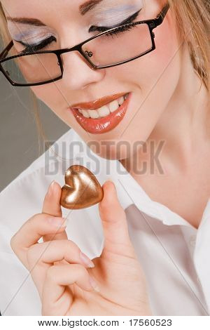 Pretty girl going to eat golden heart shaped candy