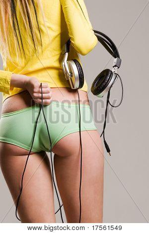 Beautiful girl holding headphones torso and legs