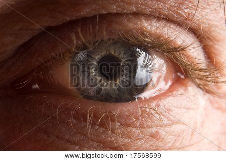 Widely open elderly man's eye closeup