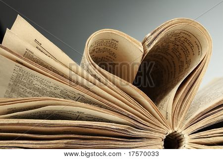 Heart in old book from yellow sheets at black background