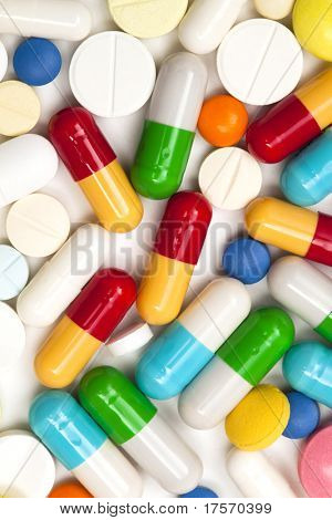 Macro shot of multi colored tablets and capsules heap isolated on white background