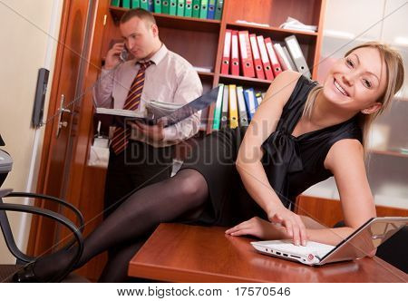 Young woman sitting on desktop with male coworker on background