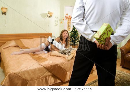 Young couple in a bedroom ready to exchange the gifts