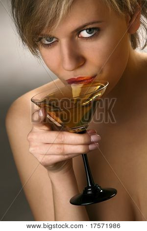 Close-up of beautiful woman with exciting red lips drinking martini cocktail