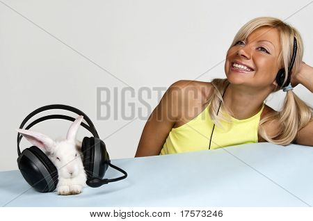 Smiling blond and white rabbit listening to music with headphones
