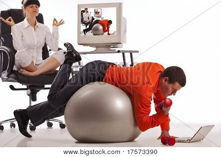 Young businessman doing push-ups with dumbbells, looking on laptop screen. His colleague, doing yoga on the office chair