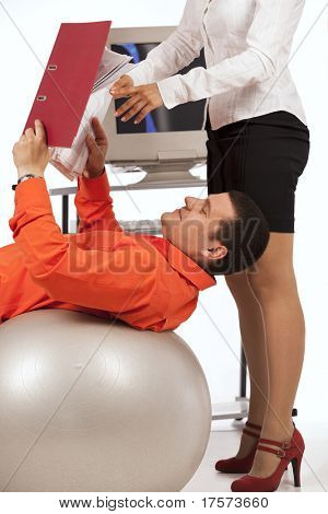 Smiling businessman doing exercise with a grey workout ball , over white background. His secretary, showing files with documents