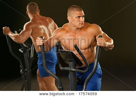 Fitness - powerful muscular man  is engaged on the xtrainer machines at the gym