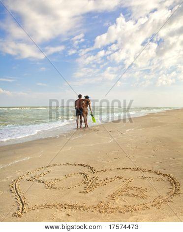 Coração desenhada na areia de uma praia (primeiro plano), o homem e a mulher em segundo plano