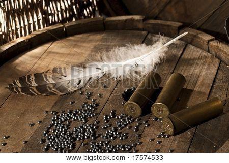 Shotgun shells and shot on wood background