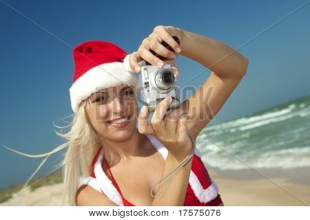 Sexy summer blond in Santa Clause suit with camera on the beach