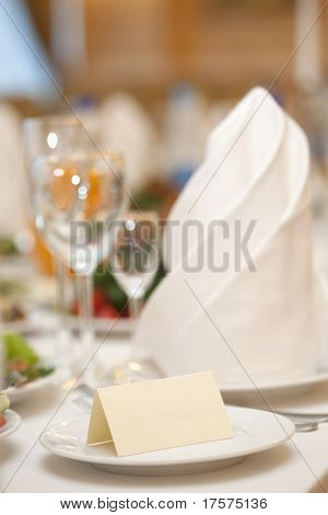A closeup of a blank wedding placecard on ceramic white plate