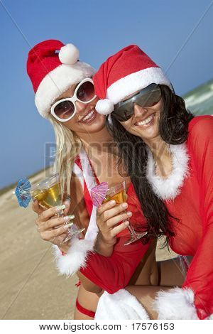 Two young sexy women in christmas suit with two martini glasses on the beachfront