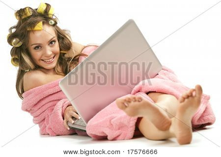 Young adult girl in pink dressing gown and with hair rollers sitting with laptop