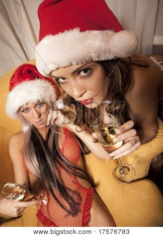 Portrait of two sexy girls in Santa hats holding the glasses of champagne