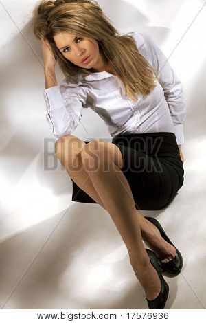 Portrait of beautiful tired woman in business suit, sitting on a floor