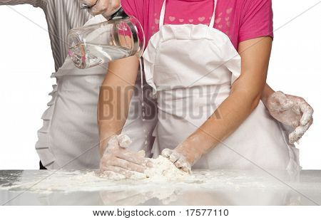 Young couple hands pouring water into flour (Focus on jug)