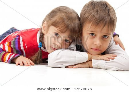 Two kids looking at something - laying flat on the floor