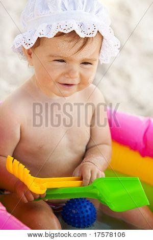 Portrait of cute little baby girl in the inflatable swimming pool with pink sunglasses