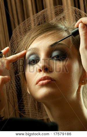 Backstage scene: Professional Make-up artist doing glamour model makeup at work