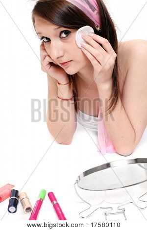 Teenage girl making make-up on a white background
