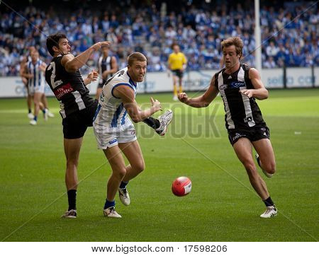 MELBOURNE - APRIL 2:  Collingwood's Alan Toovey (R) and North Melbourne' Lachlan Hansen (C) contest they ball in their match at Etihad Stadium Docklands - April 2, 2011 in Melbourne, Australia