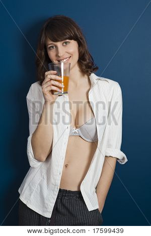 Beautiful young woman wearing a pajama against a blue wall, and drinking a orange juice