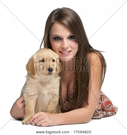 Young woman lying next to Golden Retriever puppy in front of white background