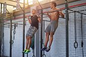 Gym partners buddies doing pull ups in a industrial looking gym, muscular fit lean men exercising poster