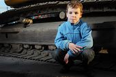 pic of night crawler  - Little boy in blue jacket sitting near crawler tractor in the dark - JPG