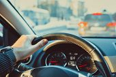 Car steering wheel with male hand. Man driving car in city concept. poster