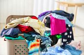 Pile of clothes in plastic laundry basket indoors poster