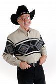 stock photo of buckaroo  - Cowboy in black hat thumbs in on belt friendly expression - JPG