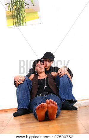 Young couple in hiphop / emo style sitting on the floor barefeet. Isolated over white. The image is slightly tilted to create dynamic.