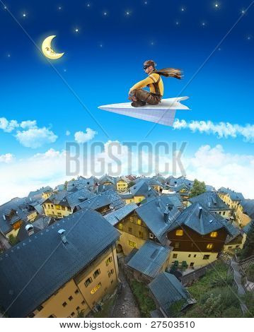 Pilot riding the paper plane above sleepy town in the moonlight