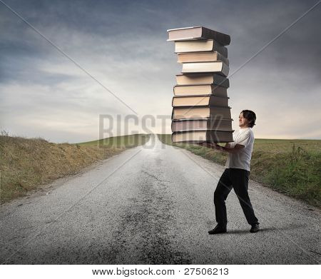 Man carrying a stack of books on a countryside road