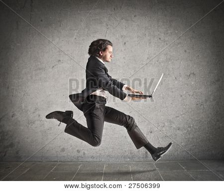 Businessman running and carrying a laptop