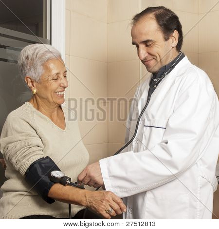 Doctor Measuring Blood Pressure Of Senior Patient At Hospital