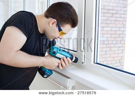 Man worker mounting window on balcony.