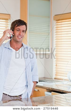 Portrait of a man making a phone call in his kitchen