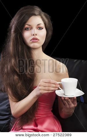 Sophisticated Lady Drinkig Tea, She Looks In To The Lens And Takes A Cup With Both Hands