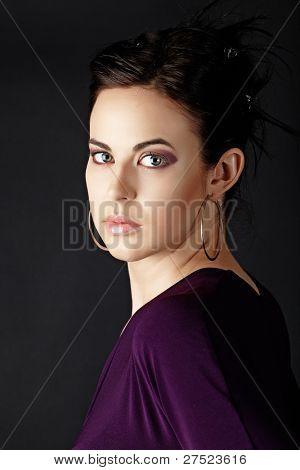 beautiful young brunette woman wearing purple dress on black studio background with dark smoky eyeshadow.