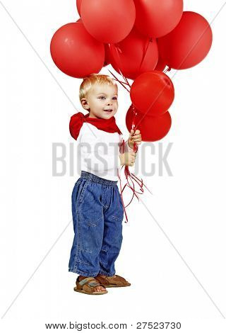 cute little boy in white shirt, jeans and red scarf smiling as he holds a bunch of red balloons