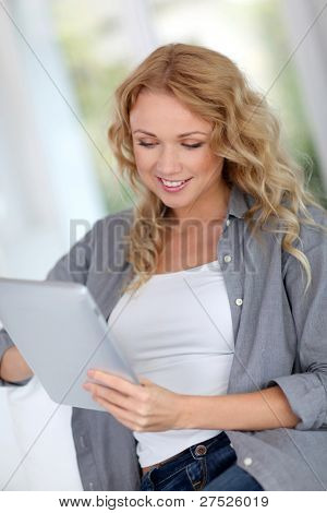 Beautiful woman at home websurfing with digital tablet