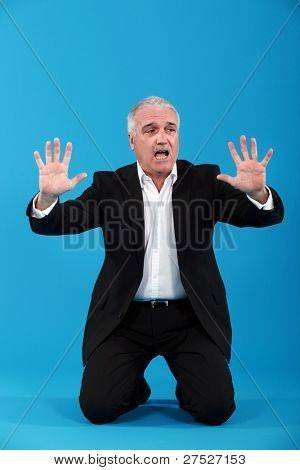 Grey haired businessman begging