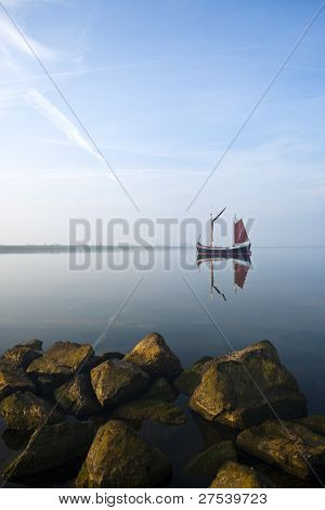 small fisher boat at lonely bay of ijsselmeer, fully reflected
