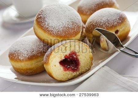 heap of marmalade filled bismarck donuts on white plate