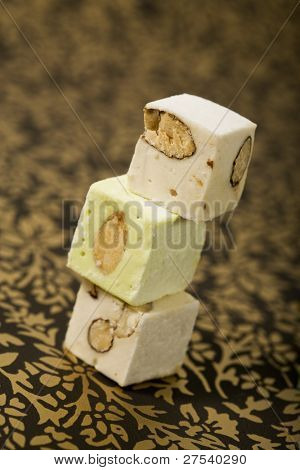 Three turron nougat confection blocks stacked on an ornamental golden surface. Turron is a typical christmas dessert in Spain and Latin America as well as in Italy, where it is called Torrone