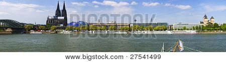 ultra wide panorama of cologne with cathedral, musical dome river Rhine, tourist boats